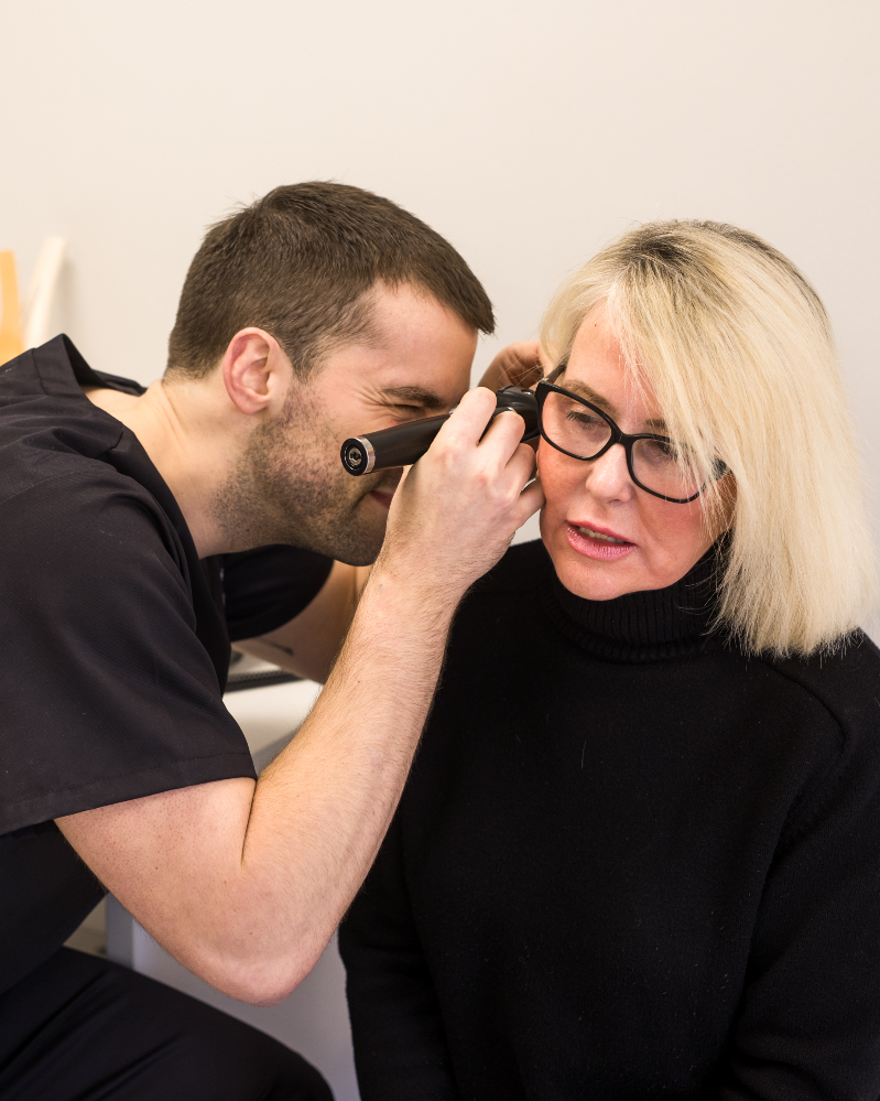 GP, Dr Gareth looking into a mature attractive woman's ear