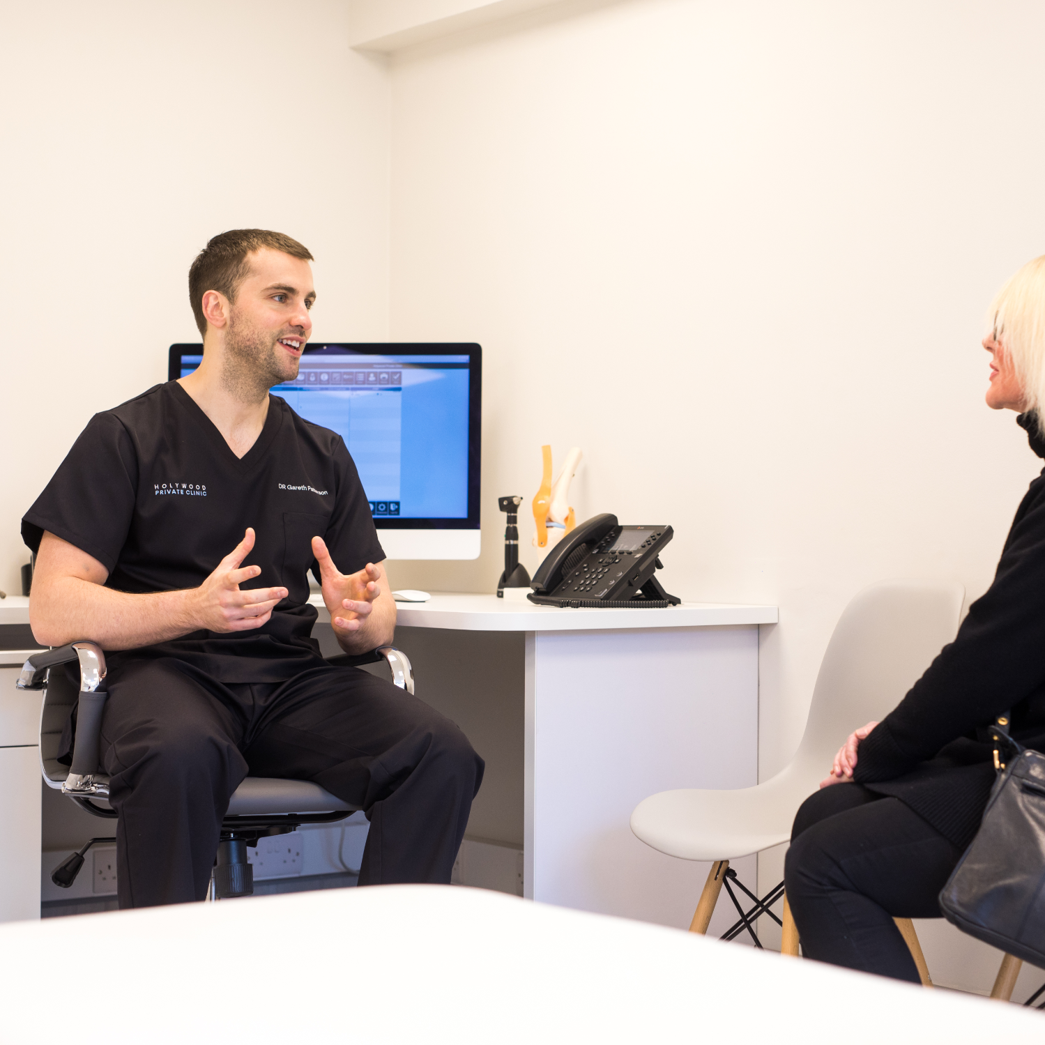 GP in a clinic talking to a patient